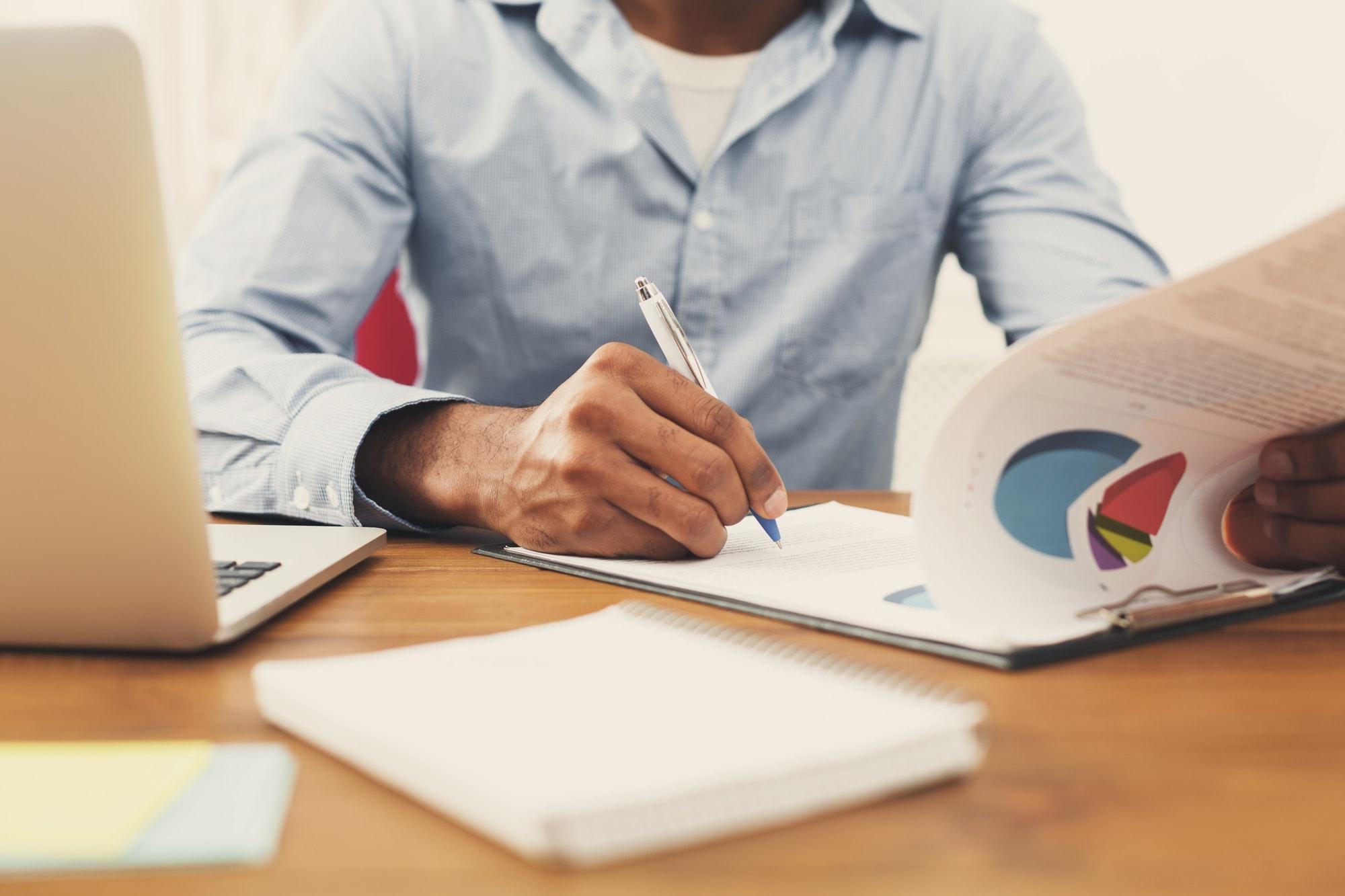 Black man reading documents in modern office
